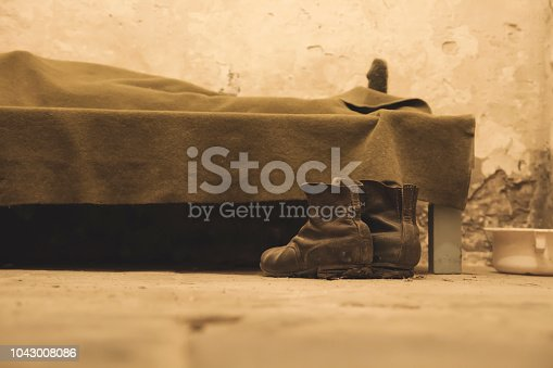 One person sleeping in a humble bedroom with a pair of old boots on the floor