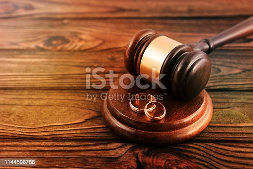 a pair of gold wedding rings, a judge's hammer on a wooden table background. family law