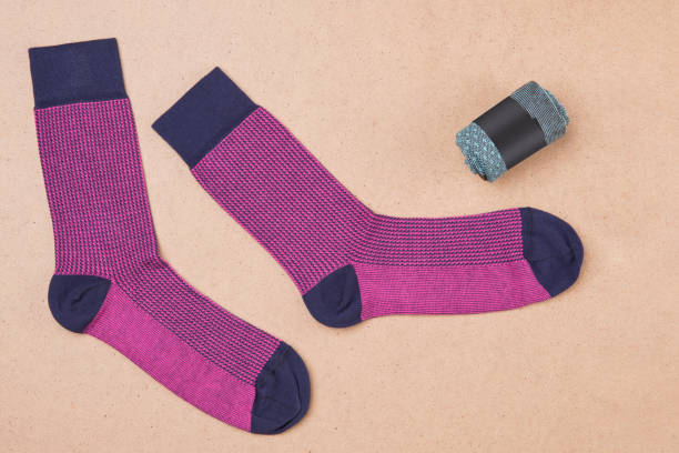 a pair of pink socks on a beige surface, next to one sock is twisted and packed, the concept a pair of pink socks on a beige surface, next to one sock is twisted and packed sock stock pictures, royalty-free photos & images
