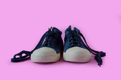 a pair of worn and dirty shoes isolated on pink