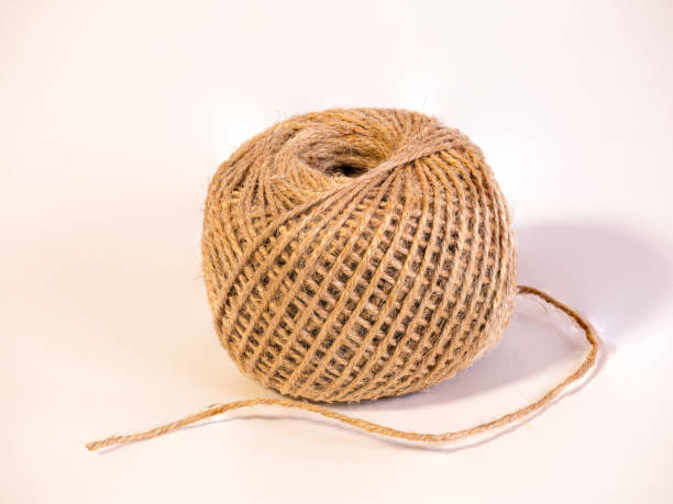 a partly uncoiled  ball of string isolated on white background