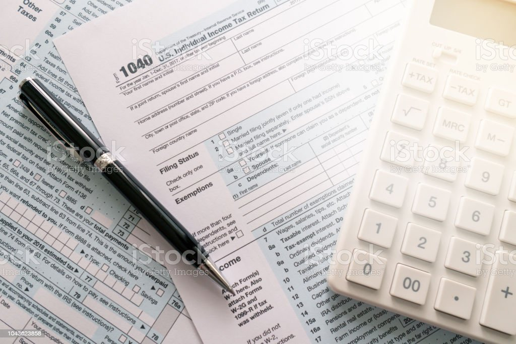 A Pen To Fill Out An Annual Tax Bill With A Calculator To Calculate