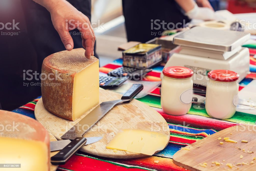 A Person Cut A Cheese In The Cheese Market Stock Photo