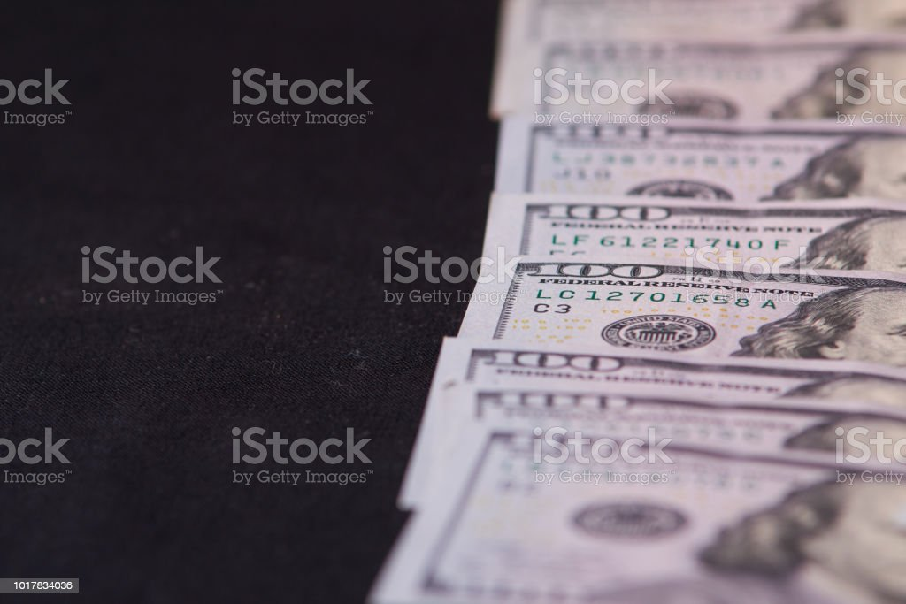 a pile of American paper hundred-dollar bills as an element of the world financial system. Selective focus stock photo
