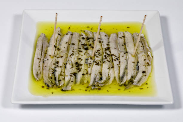 a pile of anchovies in vinegar a pile of anchovies in vinegar isolated on a white background anchovy stock pictures, royalty-free photos & images
