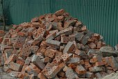 a pile of pieces of old red bricks in gray concrete on the street against a green wall
