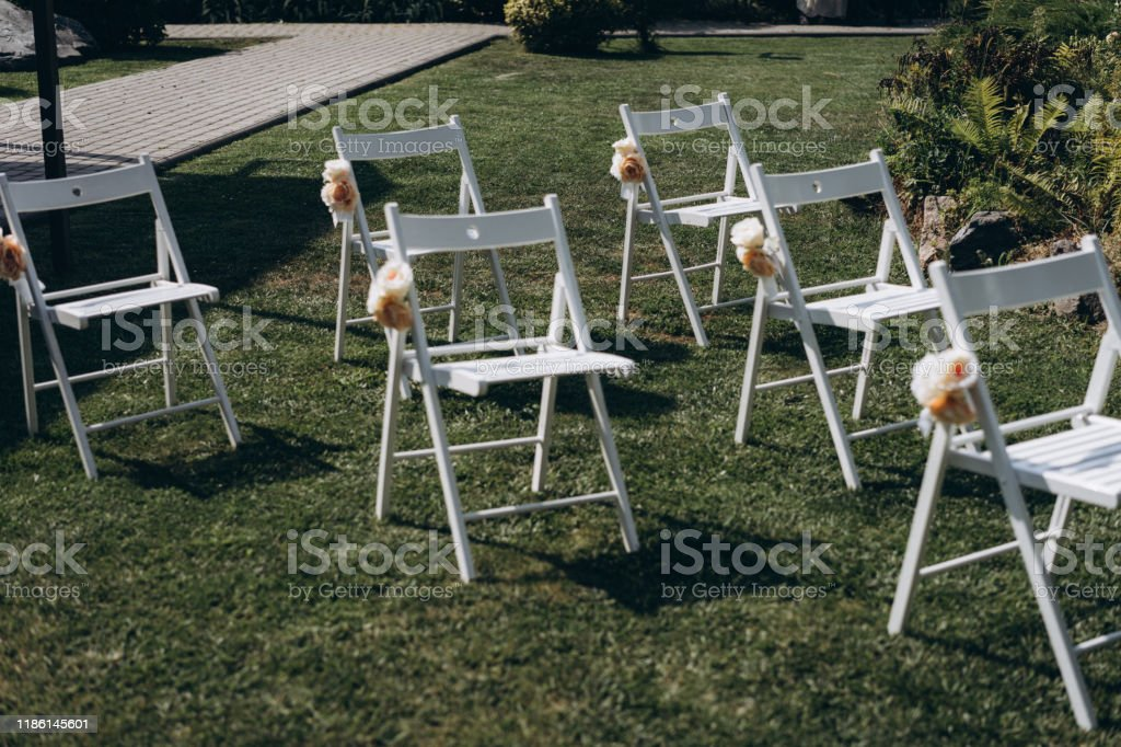 A Place For Guests At A Wedding Ceremony White Chairs Decorated With Flowers Wedding Decorations Selective Focus Film And Grain Photo Stock Photo Download Image Now Istock