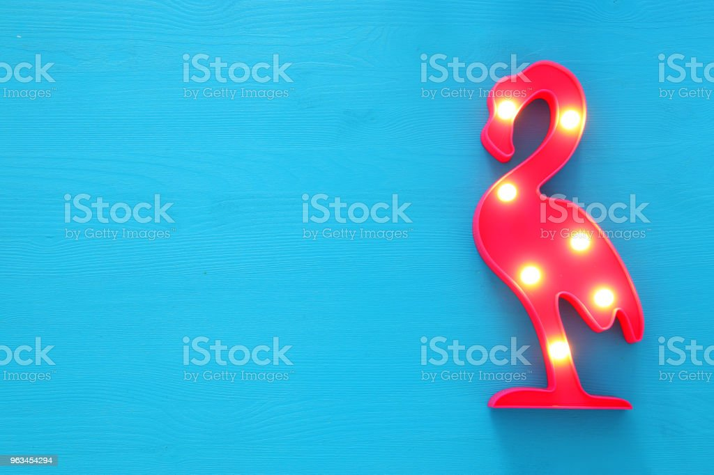 a plastic flamingo lamp with leds over blue wooden background. holiday summer concept. - Zbiór zdjęć royalty-free (Afryka)