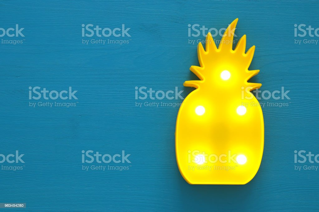 a plastic pineapple lamp with leds over blue wooden background. holiday summer concept. - Zbiór zdjęć royalty-free (Ananas)