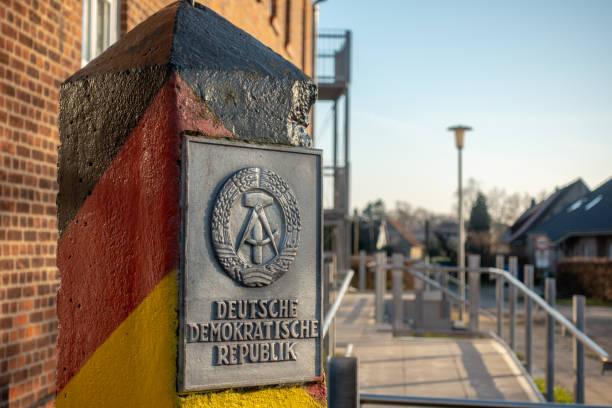 Ein Pfosten mit dem Wappen der DDR steht in einem Dorf – Foto
