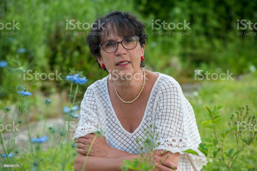 a portrait of a beautiful senior woman in the garden zbiór zdjęć royalty-free
