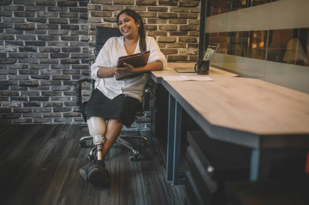 足を足首に交差させた彼女のデジタルタブレットを保持している歯の笑顔の自信を持つ彼女のワークステーションに座っている義足を持つアジアのインドのホワイトカラー労働者の肖像画 - disabilitycollection ストックフォトと画像