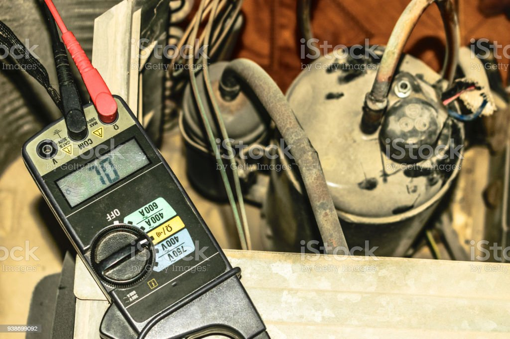 a professional ac technician is refiling the Freon into the compressor of a window air conditioner unite and the gas pressure is illuminated on the meter stock photo