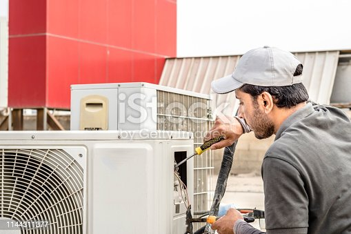 istock a professional an electrician repairman is repairing a heavy duty central air conditioner unite at the roof top 1144311377