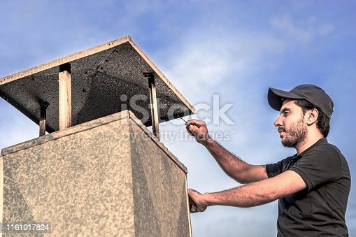 a professional carpenter man is installing a typical exhaust chimney for ventilation heavy system of kitchens  made by an aluminum at roof top and wearing blue uniform and cap