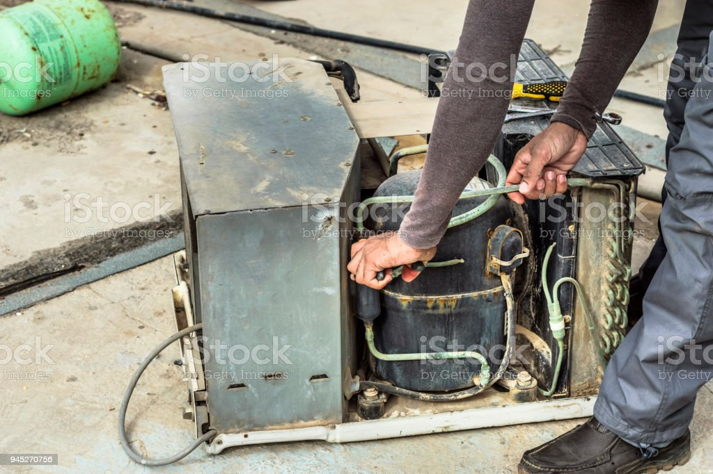 a professional electrician is repairing window air conditioning stock photo
