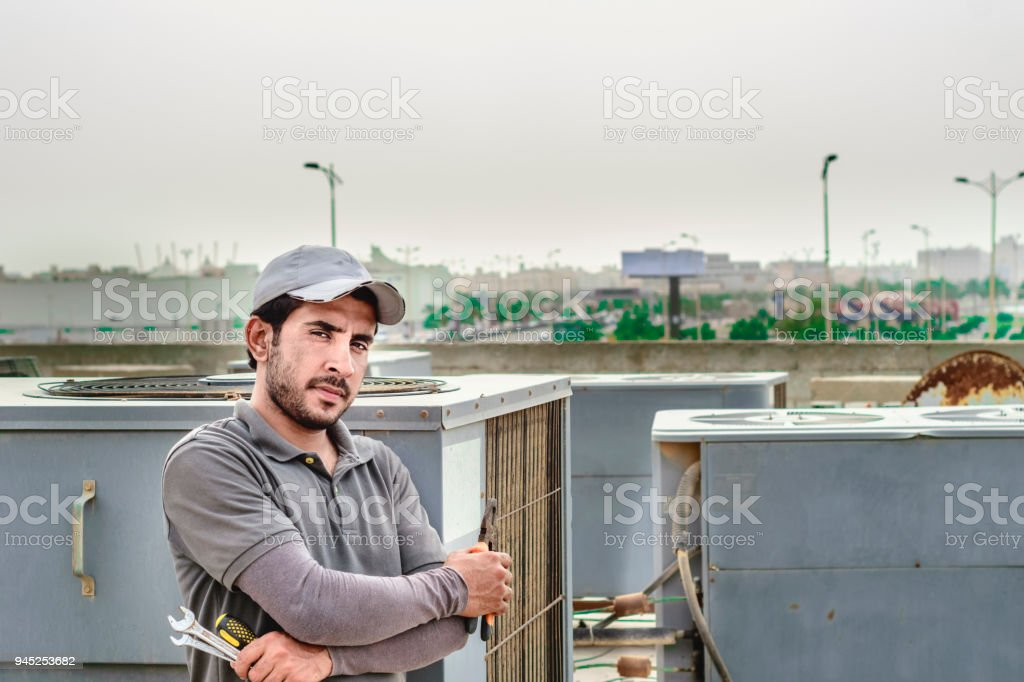 a professional electrician man is feeling proud after reparing AC units stock photo