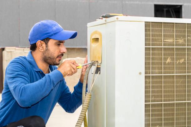 一名專業電工男子正在用他的工具在屋頂上修理中央空調系統的重型裝置, 上面戴著白色的灰色 - 恢復精神 個照片及圖片檔
