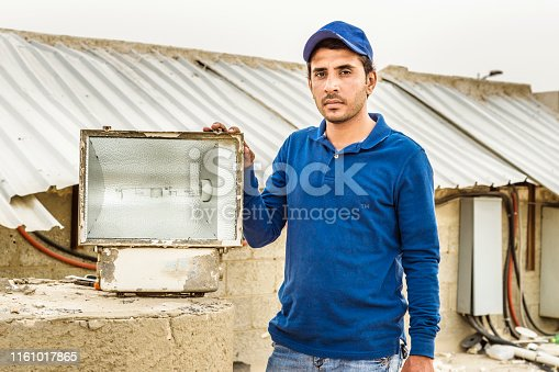 istock a professional electrician man is fixing the critical problems of electric supply of heavy duty air conditioner units on the roof top and wearing blue uniform & cap 1161017865