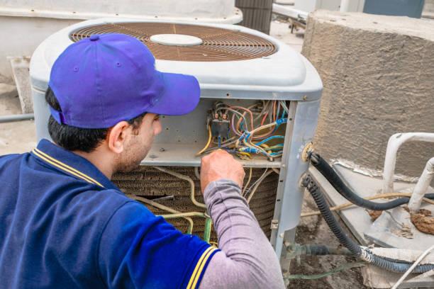 een professionele elektricien man is het opgeven van thumbs up na de vaststelling van een heavy duty airconditioner op het dak en het dragen van blauwe uniform en cap en de stad is op de achtergrond - flat cap stockfoto's en -beelden