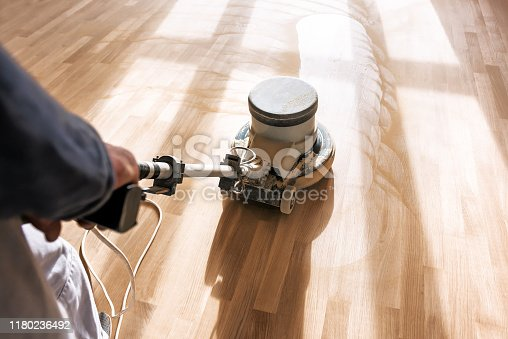 a professional master cleans the floor (parquet) with a polishing machine