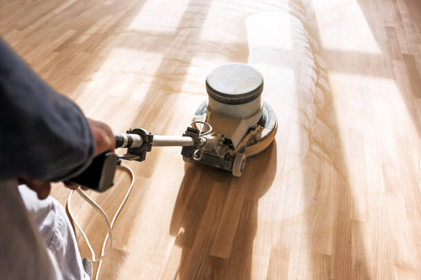 a professional master cleans the floor with a polishing machine stock photo