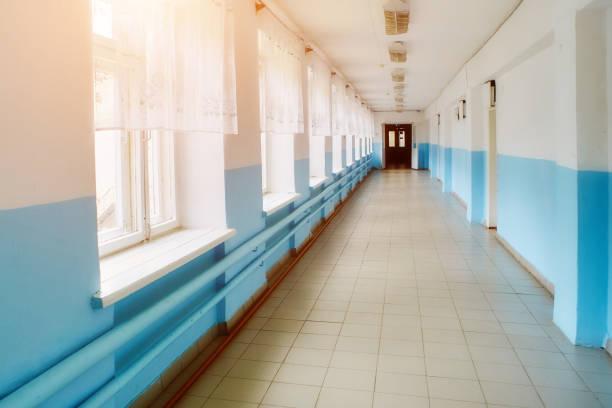 a public school, a long empty corridor with blue walls. The concept of quarantine stock photo