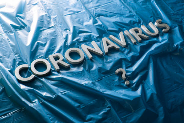 a question coronavirus laid with silver letters on crumpled blue plastic film - diagonal composition stock photo