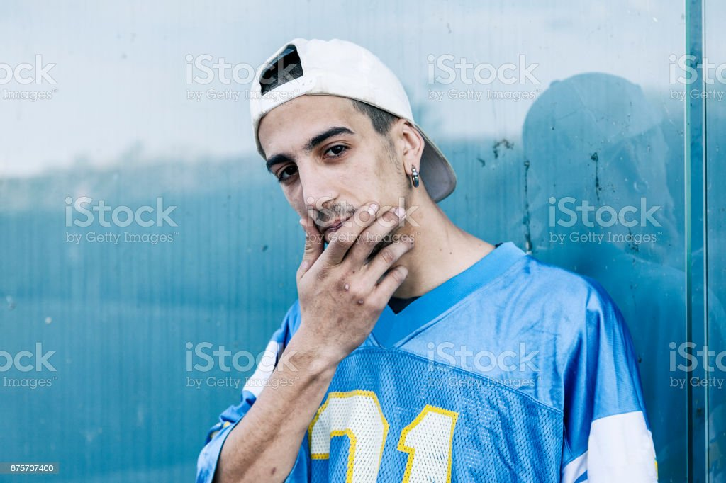 a rap singer is reflected in a blue mirror on the outskirts royalty-free stock photo
