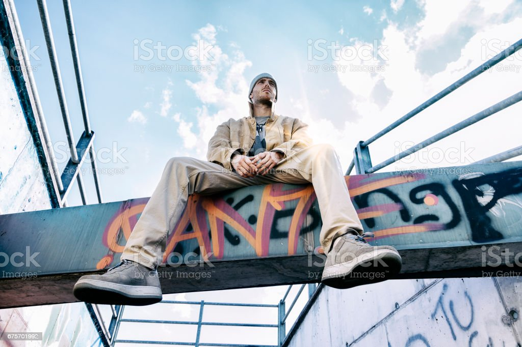 a rap singer on a concrete beam in a subway with graffiti in the background royalty-free stock photo