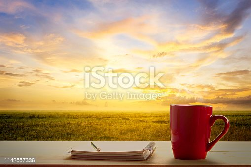 519188550 istock photo a red cup of coffee and note pad on wooden table and Empty grassland and sky at evening time 1142557336