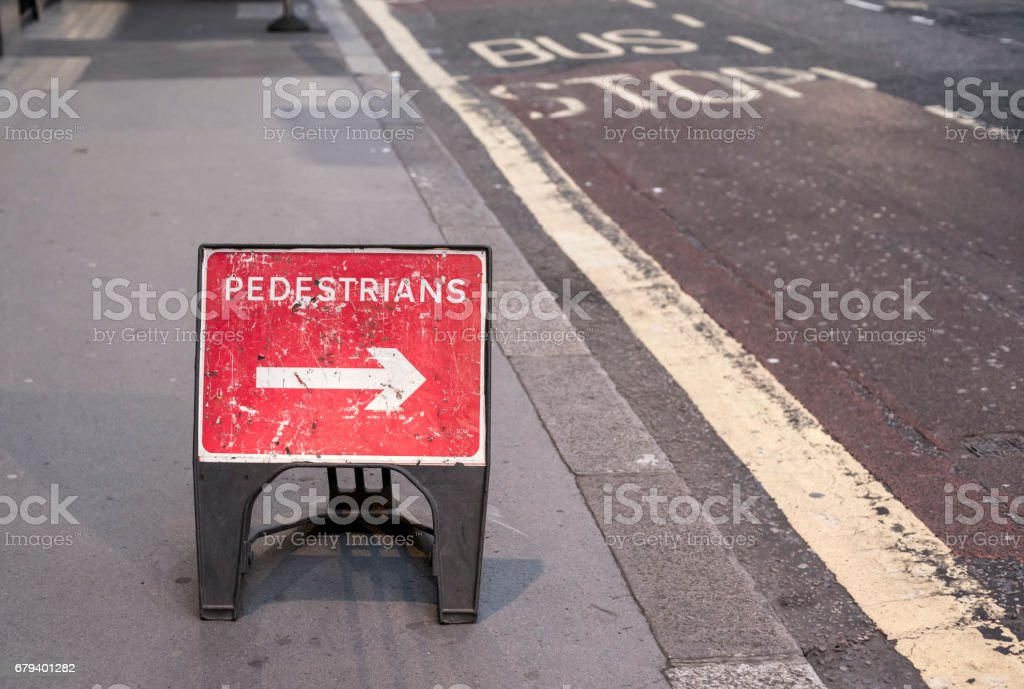 a red 'pedestrians' sign in the middle of the sidewalk, with an arrow pointing towards the road royalty-free stock photo