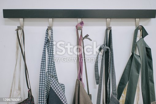 a row of apron hanging on wall at workshop