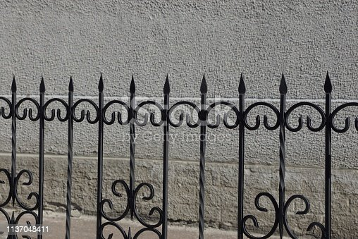 a row of black sharp iron bars of the fence against a gray wall