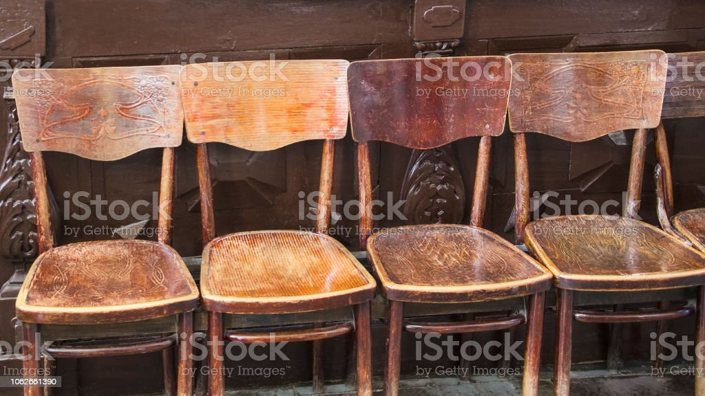 a row of brown old antique chairs in a holiday building stock photo