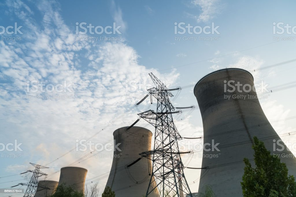 a row of cooling tower at dusk stock photo