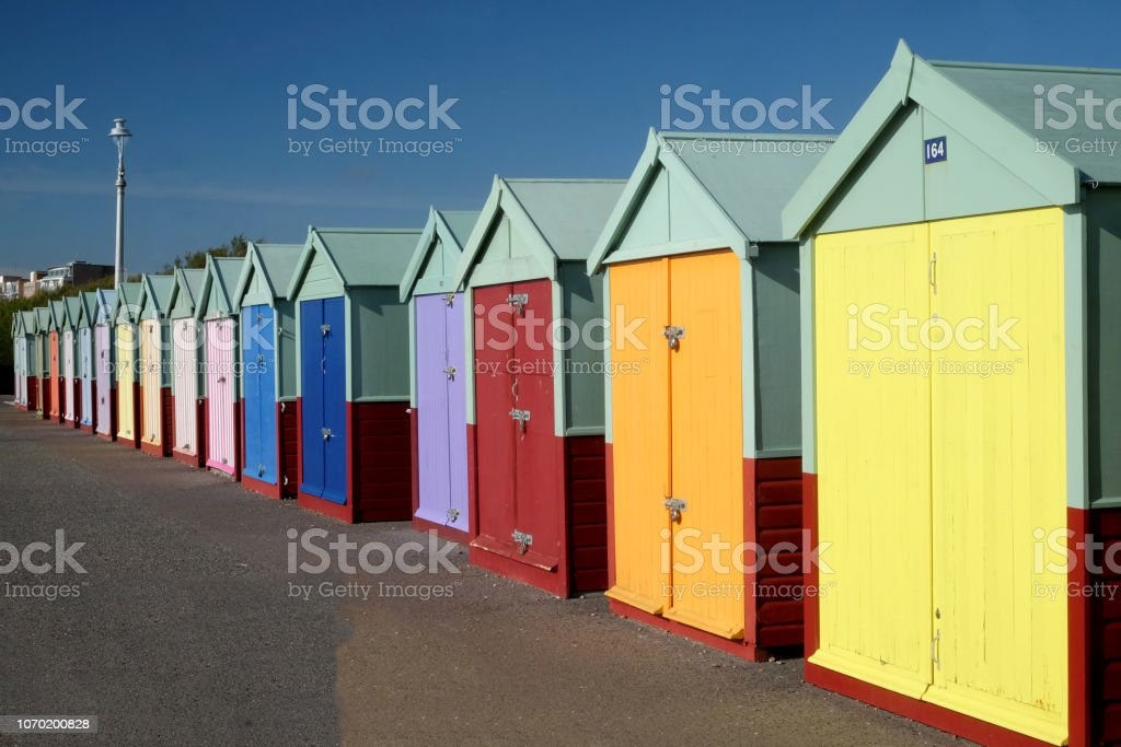 a row of sixteen colorful beach huts stock photo