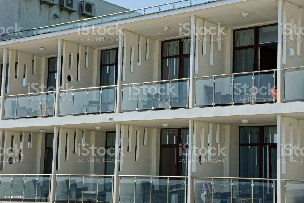 many white open glass balconies with furniture on the wall of the...