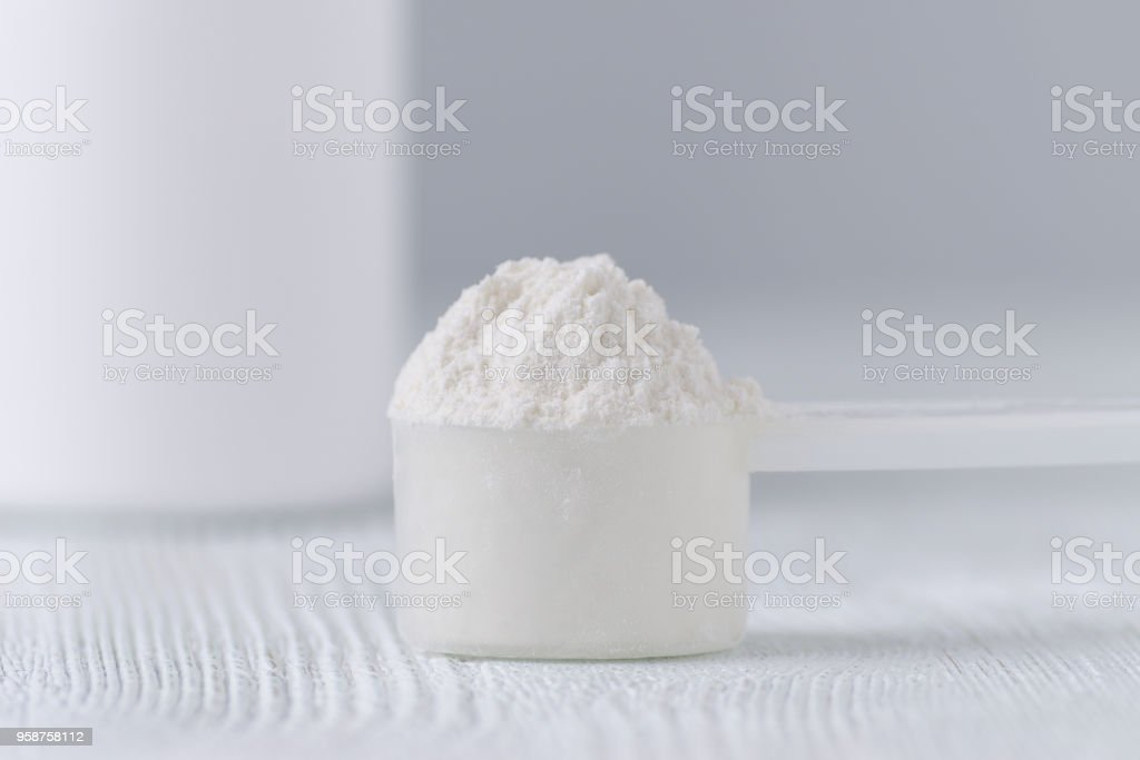 a scoop with white powder closeup and a jar on gray background stock photo