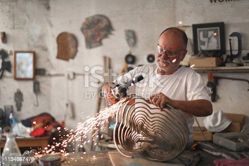 istock a Senior man creating sculptures in his art studio 1134667476