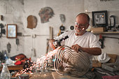 a Senior man using an angle grinder to create sculptures out of metal in his art studio.