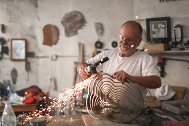 a Senior man creating sculptures in his art studio a Senior man using an angle grinder to create sculptures out of metal in his art studio. carving craft product stock pictures, royalty-free photos & images