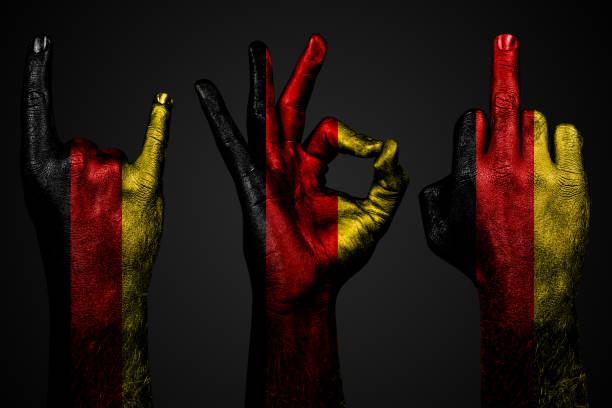 ein satz von drei händen mit einer gemalten fahne deutschland zeigt mittelfinger, ziege und okay, ein zeichen von aggression, protest und zustimmung auf einem dunklen hintergrund. - teufel berlin stock-fotos und bilder