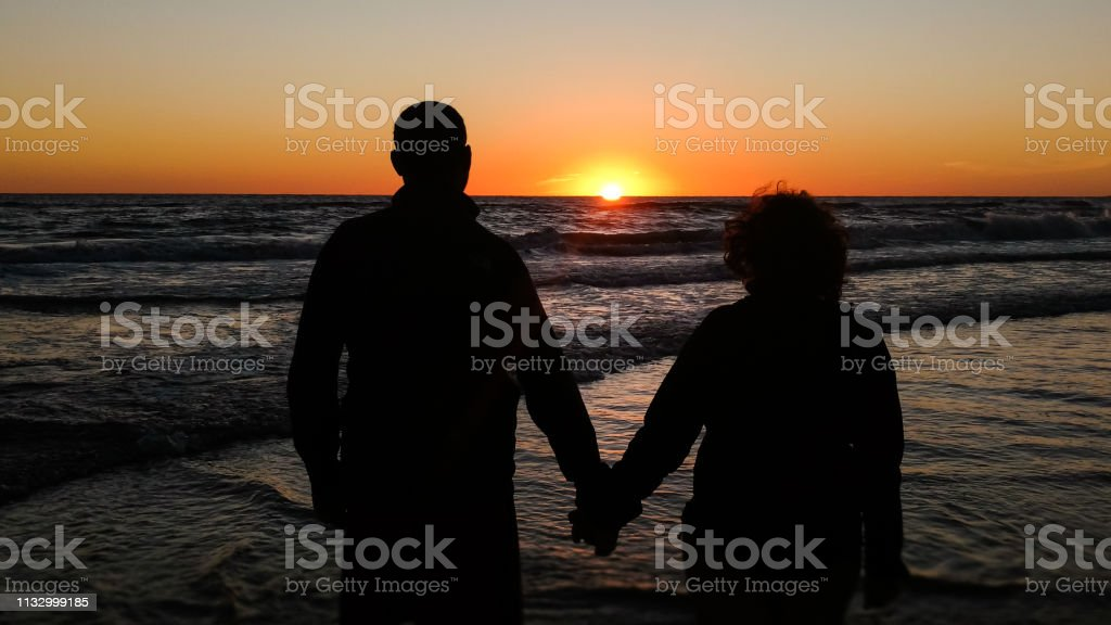 A Shadow Couple Of Lovers Enjoying A Lovely Beach Sunset Background Stock Photo Download Image Now Istock