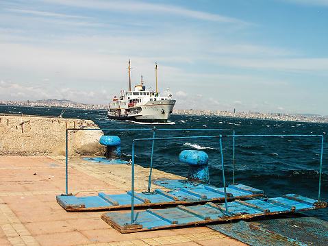 Istanbul, Turkey - September 03, 2006: a white passenger ship on wavy sea and old metal marina mooring bollard and gangway ladder on ferry terminal in a cloudy day in autumn time