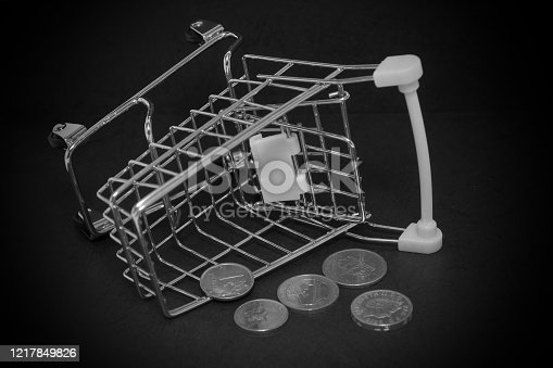 511190632 istock photo a shopping cart filled with coins of various denominations. international crisis, currency depreciation and crisis. 1217849826