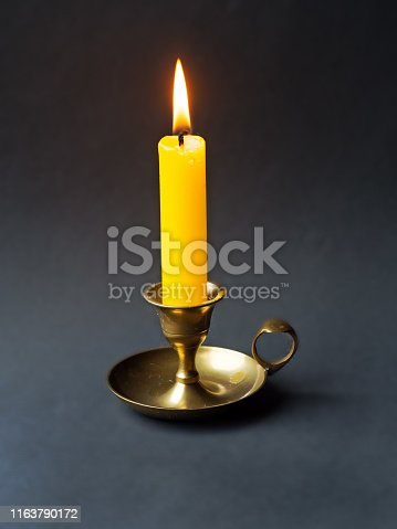 lit candle in a candlestick on a black background,