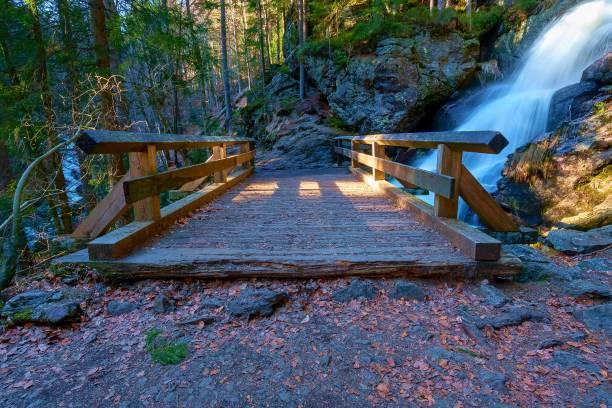 Eine kleine Brücke vor einem Wasserfall – Foto