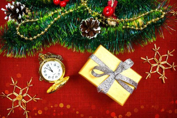 einen kleinen weihnachtsbaum lametta, nüsse, bänder und ornamente. geschenk für einen weihnachtsbaum, eine vintage-uhr. 2018 - schmuck engel stock-fotos und bilder
