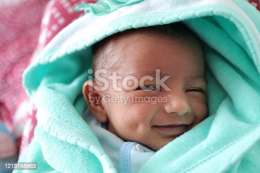 istock a smiling newborn baby with dimple in cheek wrapped in sea green colored towel with hood with eyes closed with selective focus on front eye. 1215168963